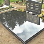 bis auf einen kleinen Pflanzstreifen komplett abgedeckte Grabanlage