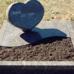Schriftstein in Herzform mit teilabgedeckter Grabstelle