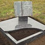 Grabmal in Buchform mit Stütze auf Grabplatte